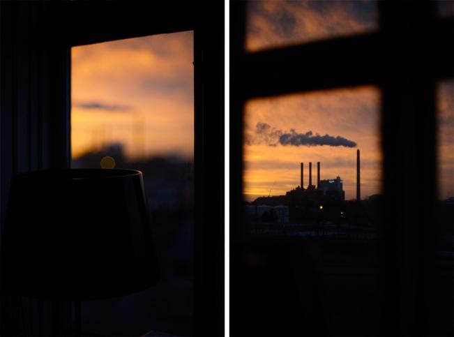 Urban sunrise seen through windows with chimneys against the peach sky